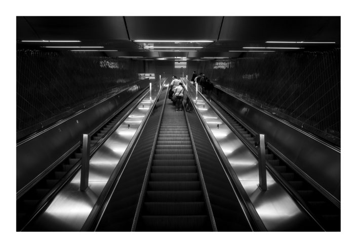 Rolltreppe mit Menschen, schwarz weiß Foto, Spotlight in der Mitte, Tom Brunner