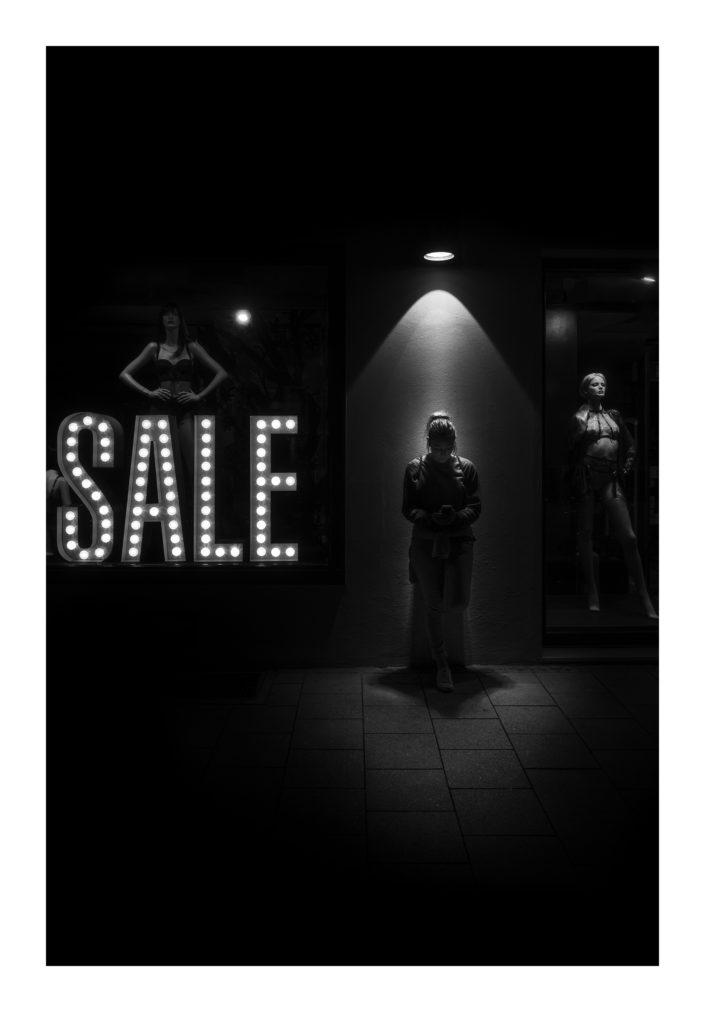 Schaufenster mit Figuren, Frau im Spotlicht unter einen Lampe, schwarz weiß, Tom Brunner