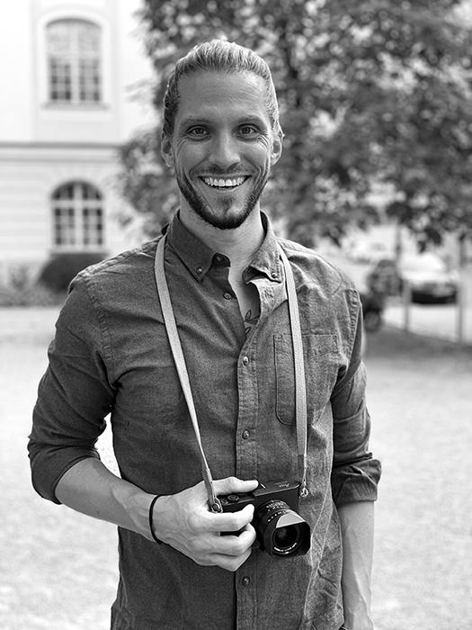 Fotograf Tom Brunner mit Kamera, schwarz weiß Foto