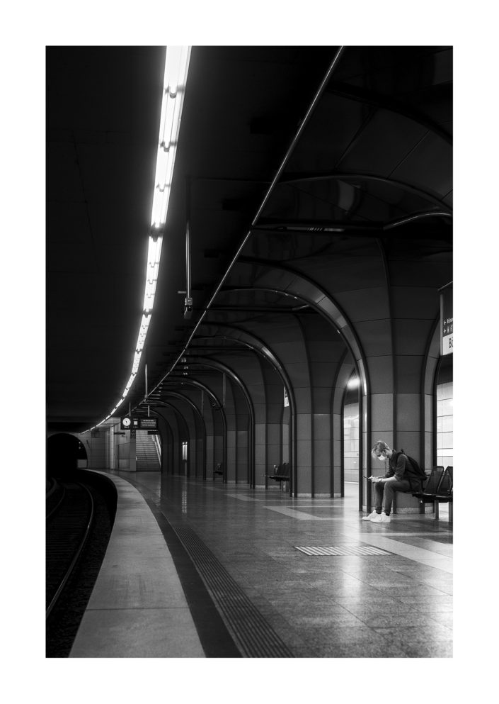 Mann in Bahnstation wartet auf Zug, führende Linien, schwarz weiss, Tom Brunner