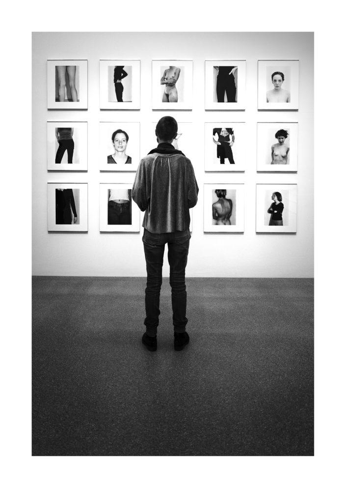 Frau betrachtet Bilder an der Wand, Streetphotography, schwarz weiß, Tom Brunner