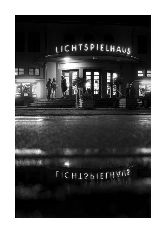 drei Menschen vor Kino, Spiegelung des Schriftzugs, schwarz weiß Foto, Tom Brunner