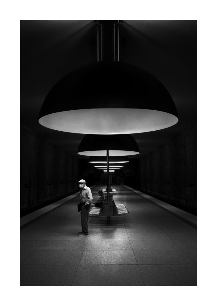 Bahnstation mit Mann der angestrahlt wird, Architektur, schwarz weiß, Tom Brunner