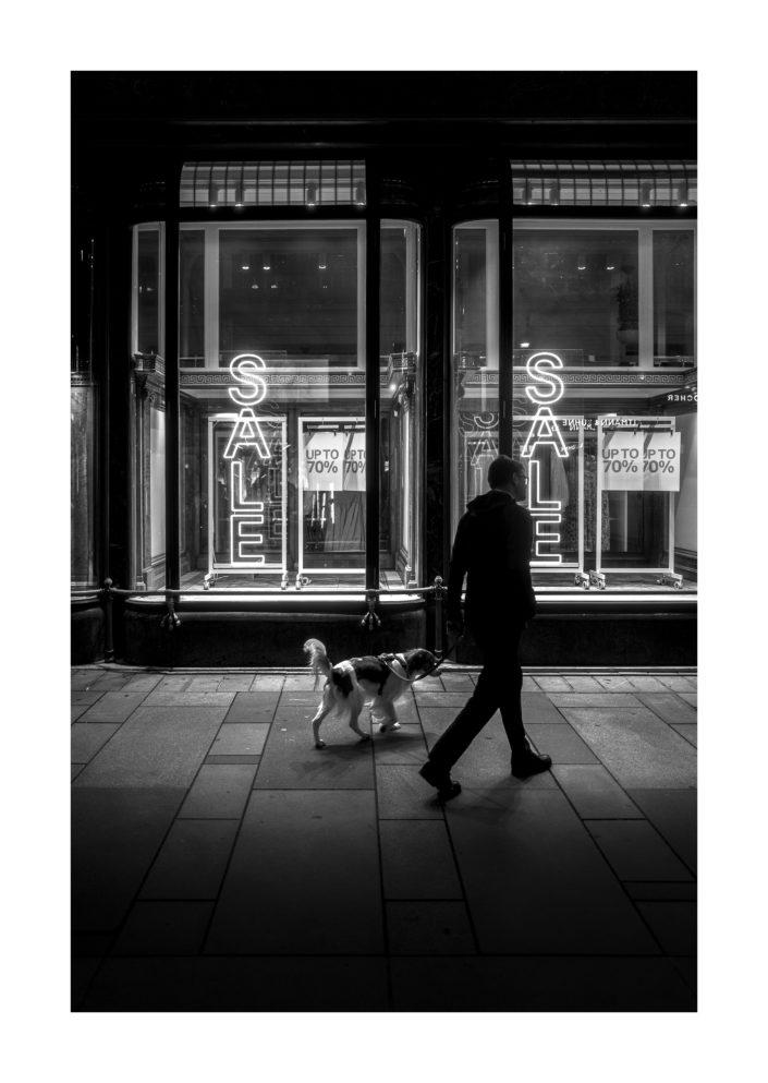 Mann mit Hund vor Schaufenster mit Sale Reklame, schwarz weiß Foto, Tom Brunner